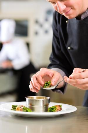 keuken restaurant: Chef-kok in het hotel of restaurant keuken koken, is hij bezig met het afwerken van een schotel
