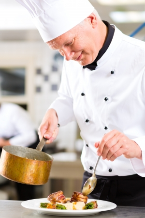 chef cooking: Chef in hotel or restaurant kitchen cooking, he is working on the sauce for the food as saucier