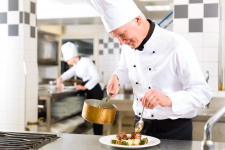 cooking pot: Chef in hotel or restaurant kitchen cooking, he is working on the sauce for the food as saucier