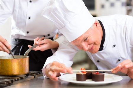 Cook, the pastry chef, in hotel or restaurant kitchen cooking, he is finishing a sweet dessert Stock Photo - 15120015