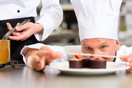 Cook, the pastry chef, in hotel or restaurant kitchen cooking, he is finishing a sweet dessert photo