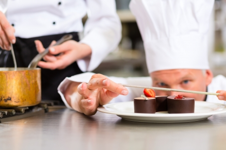 Cook, the pastry chef, in hotel or restaurant kitchen cooking, he is finishing a sweet dessert Stock Photo - 15119952