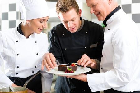 Chef team in restaurant kitchen with dessert working together photo