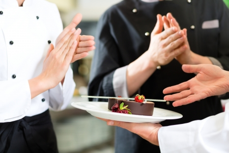 sweet pastries: Chef team in restaurant kitchen with dessert, the colleagues applauding because the dish works great Stock Photo