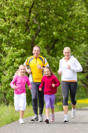 weekend activities: Family jogging for sport outdoors with the kids on summer day