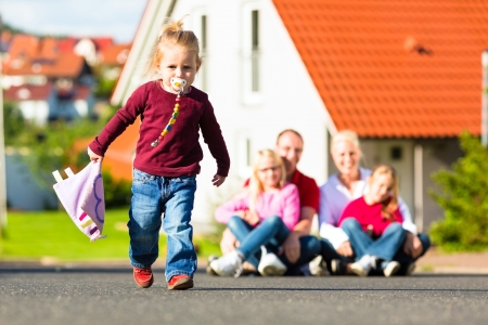 rural home: Young family sitting in the sun in front of their new home, their baby running in front Stock Photo