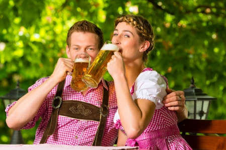 Happy Couple sitting in Beer garden in summer and enjoy a glass of beer and the sun photo