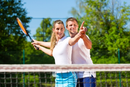 tennis net: Man, tennis teacher, showing woman how to play the racket sport outdoors