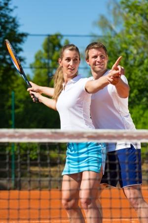 racket sport: El hombre, profesor de tenis, muestra a la mujer como jugar al aire libre del deporte de raqueta