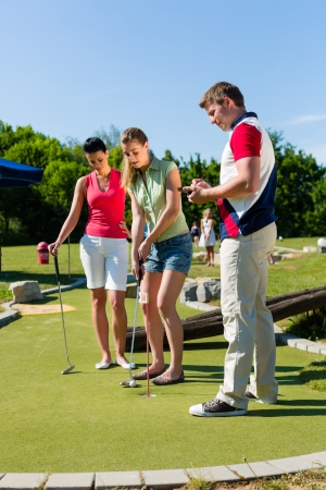 People, man and women, playing miniature golf on a beautiful summer day photo