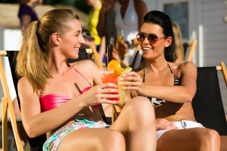 People at beach drinking having a party, two girls clinking glasses with cocktails having fun photo