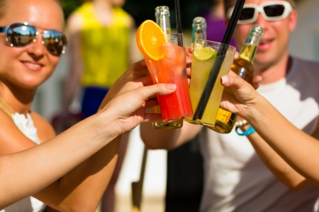 jovenes tomando alcohol: La gente en la playa bebiendo una fiesta, los amigos que tintinean los vidrios con los cocteles y cervezas que se divierten