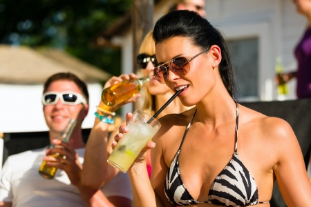 beach drink: People at beach drinking having a party, woman or girl in front drinking cocktail