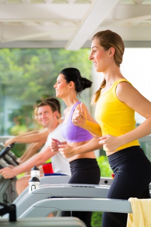 health club: Running on treadmill in gym or fitness club - group of women and men exercising to gain more fitness
