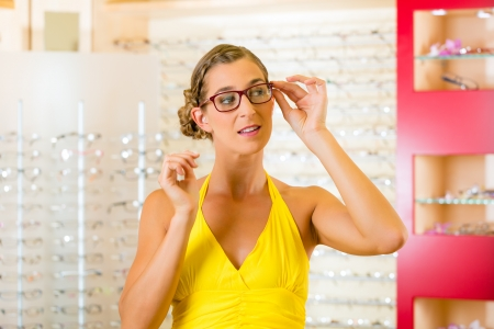 wearer: Young woman at optician with glasses, she might be customer or salesperson Stock Photo
