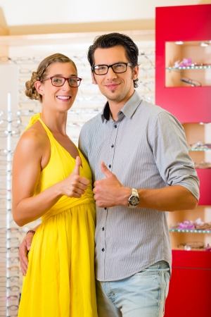 Young couple at optician in the store, they looking for glasses, thumps up photo