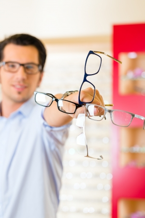Young man at optician with glasses, he might be customer or salesperson photo