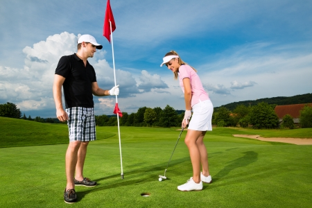golfing: Young sportive couple playing golf on a golf course, she is putting at the green Stock Photo