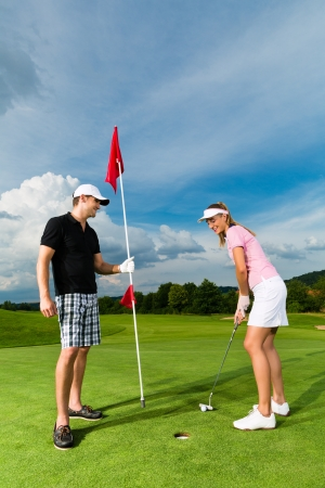 Young sportive couple playing golf on a golf course, she is putting at the green photo