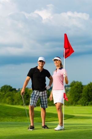 Young sportive couple playing golf on a golf course, they certainly do exercise or have training photo