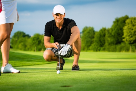 golf man: Young golf player on course putting, he aiming for his put shot