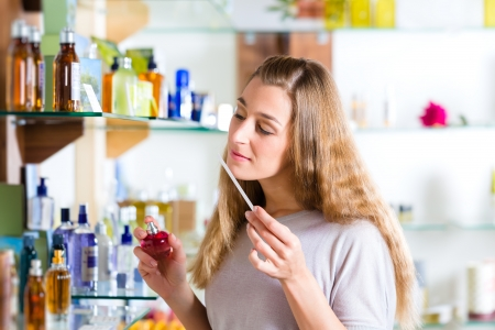 Young woman buying perfume in a shop or store, testing the fragrance with a paper tester Stock fotó