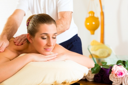 male massage: Woman enjoying a wellness back massage in a spa, she is very relaxed (close-up) Stock Photo
