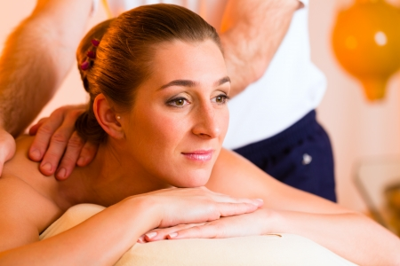 Woman enjoying a wellness back massage in a spa, she is very relaxed  photo