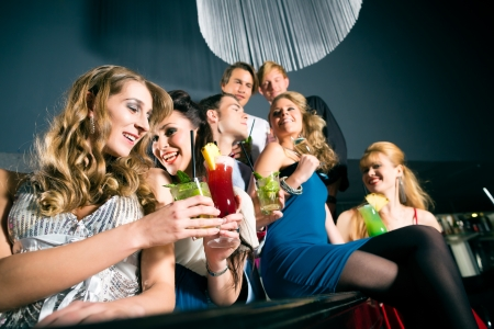 flirting: Young people in club or bar drinking cocktails and having fun Stock Photo