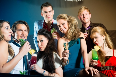 clique: Young people in club or bar drinking cocktails and having fun Stock Photo
