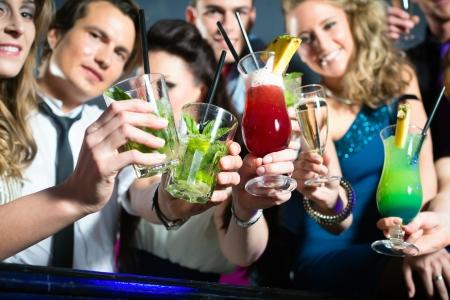 Jonge mensen in club of bar cocktails drinken en plezier maken