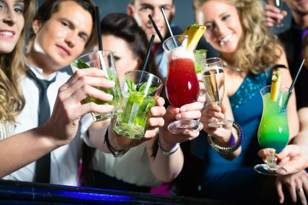 cocktail party: Young people in club or bar drinking cocktails and having fun Stock Photo