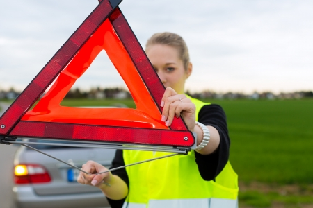 warning triangle: Young woman with warning triangle on street after a car breakdown Stock Photo