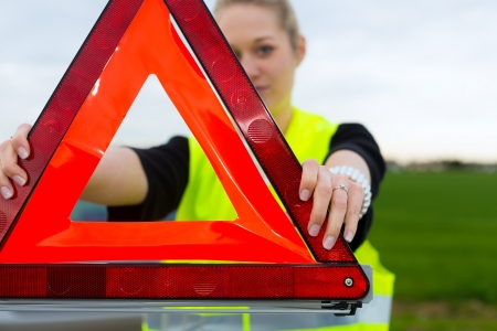 Young woman with warning triangle on street after a car breakdown Stock Photo - 15479879