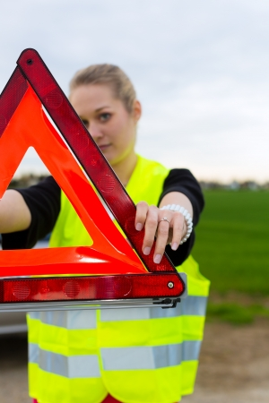 Young woman with warning triangle on street after a car breakdown photo
