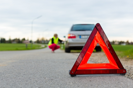 Young woman with warning triangle on street after a car breakdown Stock Photo - 15479956