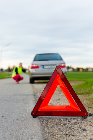 Young woman with warning triangle on street after a car breakdown Stock Photo - 15479919