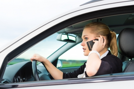 Young woman with telephone having phone conversation while driving car photo