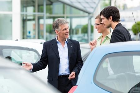 Mature Autoh�ndler und junge Paar steht auf Parkplatz am Autohaus vor Autos