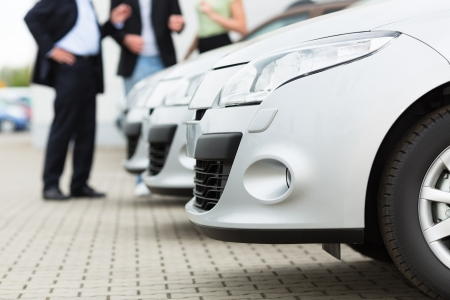 car dealers: Two men man and one woman stand behind a row of silver-metallic cars on a parking place on yard of dealer
