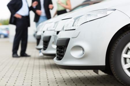 Zwei M�nner Mann und eine Frau hinter einer Reihe von Silber-Metallic-Autos stehen auf einem Parkplatz auf dem Hof ??des H�ndlers Lizenzfreie Bilder