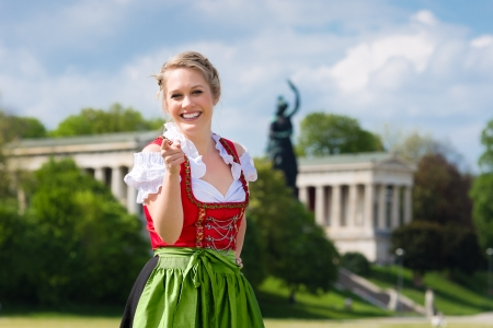 dirndl: Young woman in traditional Bavarian clothes - dirndl or tracht - in front of Bavaria in Munich Stock Photo