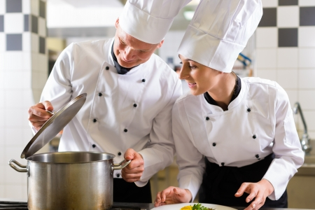 commercial kitchen: Two chefs - man and woman - in hotel or restaurant kitchen working and cooking in team
