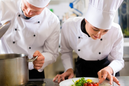chef cooking: Two chefs - man and woman - in hotel or restaurant kitchen working and cooking in team