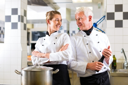 Two chefs - man and woman - in hotel or restaurant kitchen working and cooking in team Stock Photo - 15479925