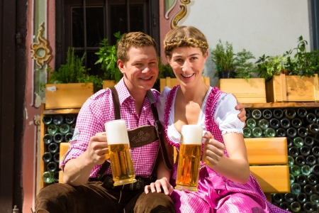 stein: Happy Couple sitting in Beer garden in summer and enjoy a glass of beer and the sun