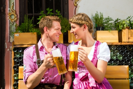 traditional costume: Happy Couple sitting in Beer garden in summer and enjoy a glass of beer and the sun