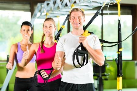 Gruppe von Menschen trainieren mit Schlingentrainer oder Suspension Trainer im Fitnessstudio