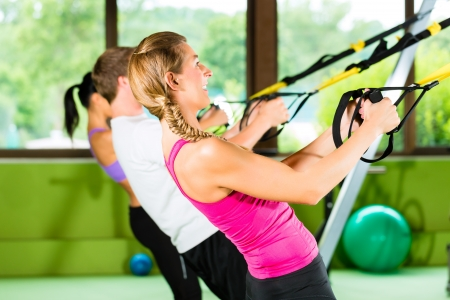 Group of people exercising with suspension trainer in fitness club or gym Stock Photo - 15479913