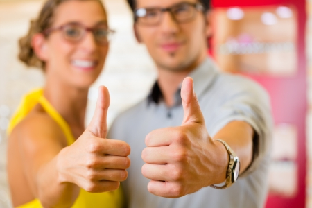 wearing glasses: Young couple at optician in the store, they looking for glasses, thumps up